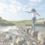 woman on stepping stones over water