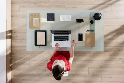 top view of a woman sitting at tidy desk and working on her laptop