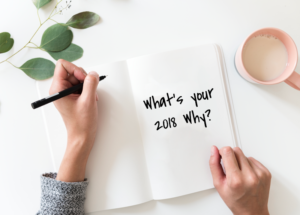 woman writing in journal what's your why 2018